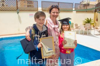 A mother with her 2 children who have both completed a language course