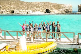 A group of students waving next to a boat at the Blue Lagoon, Comino