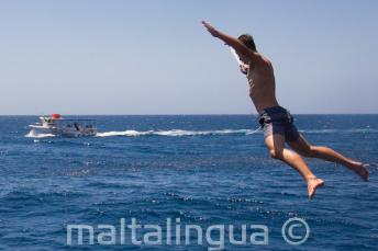 A student doing a star jump from the boat