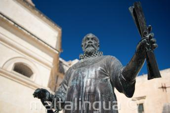 A statue in Malta of a man holding a scroll
