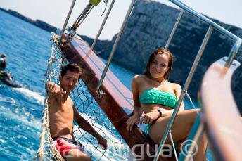 2 students lounging on the deck of a boat at Comino in Malta.