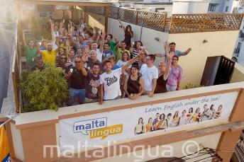 English language students waving on the school's rooftop terrace