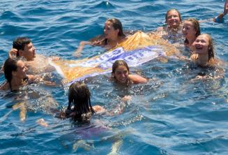 English school group leaders swimming with studetns