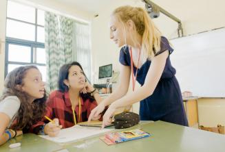 A teacher explaining an English language point to 2 students