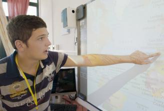 A student pointing to a map in class