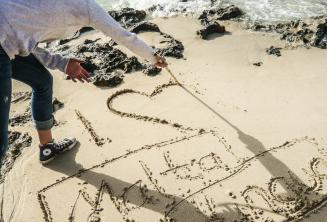 A student writing I 'heart' Maltalingua in the sand
