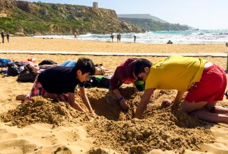 Group leader and kids digging a hole at the beach
