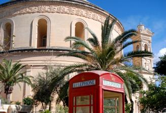 A red telephone box in front of the Mosta Rotunda