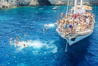 Language students jumping off a boat at Crystal Bay, Comino.