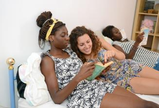 A student reading a book with a member of the host family