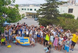 A large group of junior students waving outside the summer school